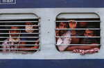 FILE - In this Saturday, May 23, 2020, file photo, migrant workers look out a train window before moving to their home states, at a railway station in Hyderabad, India. The head of India's massive railway system said Friday, May 29, that authorities are investigating whether some migrant workers died of starvation or sickness this week while traveling on special trains to their home villages in blazing heat after losing their jobs in cities because of the coronavirus lockdown. Railway Board Chairman Vinod Kumar Yadav said more than 5 million migrant workers and their families this month from cities and towns to their home villages on 3,840 trains. (AP Photo/Mahesh Kumar A., File)