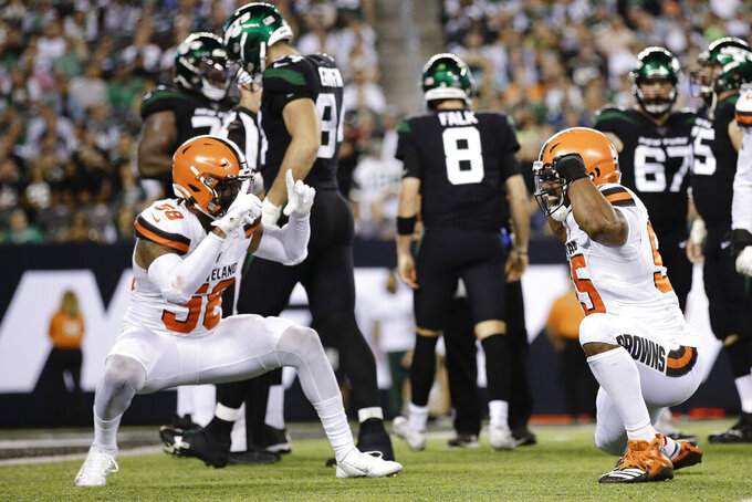 Cleveland Browns' Christian Kirksey (58) celebrates with Myles Garrett (95) after Garrett sacked New York Jets' quarterback Luke Falk (8) during the second half of an NFL football game Monday, Sept. 16, 2019, in East Rutherford, N.J. (AP Photo/Adam Hunger)
