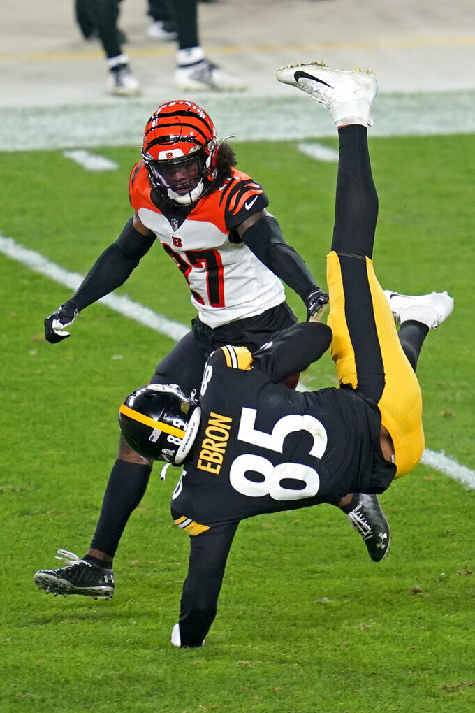 Pittsburgh Steelers tight end Eric Ebron (85) is upended with Cincinnati Bengals defensive back Tony Brown (27) defending during the first half of an NFL football game, Sunday, Nov. 15, 2020, in Pittsburgh. (AP Photo/Keith Srakocic)