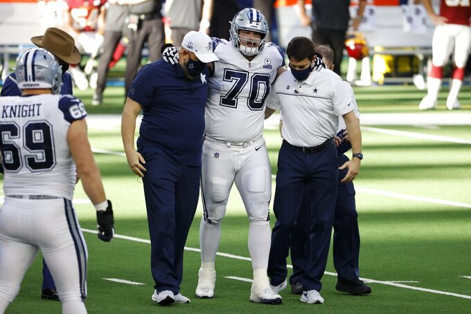 Dallas Cowboys guard Zack Martin (70) is assisted off the field by team medical staff after suffering an unknown injury in the first half of an NFL football game against the Washington Football Team in Arlington, Texas, Thursday, Nov. 26, 2020. (AP Photo/Ron Jenkins)