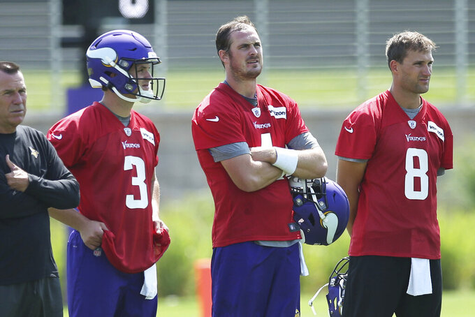 Minnesota Vikings quarterbacks, from left, Jake Browning, Sean Mannion and Kirk Cousins take a break during the NFL football team's training camp which opened with rookies and select veterans Tuesday July 23, 2019, in Eagan, Minn. (AP Photo/Jim Mone)