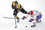 Montreal Canadiens center Nate Thompson (44) knocks the puck away from Boston Bruins left wing Anders Bjork (10) during the first period of an NHL hockey game in Boston, Wednesday, Feb. 12, 2020. (AP Photo/Charles Krupa)