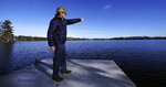 "In this Dec. 27, 2018, photo, Murray Beach, an investment banker who lives on the shore of Willett Pond, points out the spillway of the lake, which is located on the border of Norwood and Walpole, Mass. The spillway at the 107-year-old Willett Pond Dam is capable of handling just 13% of the water flow from a serious flood before the dam is overtopped, according to a recent state inspection report. ""We are not talking of just flooding someone's house. We are talking about covering their house,"" said Beach, who belongs to a citizens group that has lobbied for years for the spillway to be repaired. (AP Photo/Charles Krupa)"