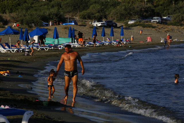A father with his child walks along Saint Rafael beach in southern coastal city of Limassol, Cyprus, on Wednesday, July 29, 2020. Cyprus' Tourism Minister Savvas Perdios says the country doesn't expect to receive this year more than 20-25% of the record 3.97 million holidaymakers it welcomed in 2019 as the coronavirus pandemic has so far shut out its key tourism markets. (AP Photo/Petros Karadjias)