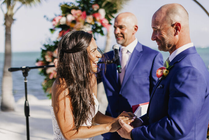CORRECTS POSITION OF LAGE TO CENTER - Associated Press sportswriter Larry Lage, center, officiates the wedding of Ryan Rutledge and Natalie LaRocca, left, at the Postcard Inn Beach Resort and Marina in Islamorada, Fla. on March 27, 2021. (Photo courtesy of Lukas Guillaume via AP)