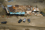 In this aerial photo, workers clear debris near the remains of a damaged building in the aftermath of Hurricane Ida, Monday, Sept. 6, 2021, in Grand Isle, La. (AP Photo/Matt Slocum)