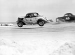 "FILE - In this Feb. 14, 1953, file photo, Red Farmer (61) of Miami, is airborne after hitting a hole on the four-mile road course during the 100-mile Modified and Sportsmen stock car auto race in Daytona Beach, Fla. NASCAR is being heavily promoted by a broadcast partner as about to embark on ""The Best Season Ever"" and on paper that could be true. NASCAR this year will race on dirt for the first time since 1970, the schedule includes a whopping seven road courses and five venues new to the Cup Series. Michael Jordan and Pitbull are among new team owners entering the sport in 2021 and Chase Elliott, NASCAR's most popular driver, is the reigning champion.  (AP Photo/James P. Kerlin, File)"