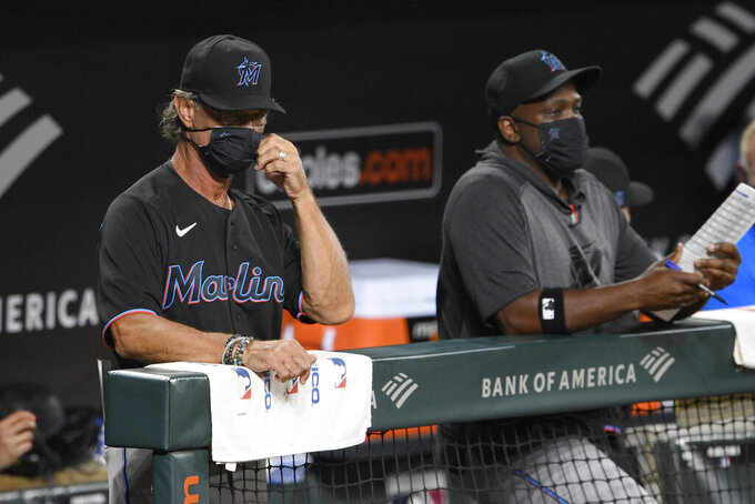 Miami Marlins manager Don Mattingly, left, adjusts his face mask during the third inning of a baseball game against the Baltimore Orioles, Thursday, Aug. 6, 2020, in Baltimore. (AP Photo/Nick Wass)