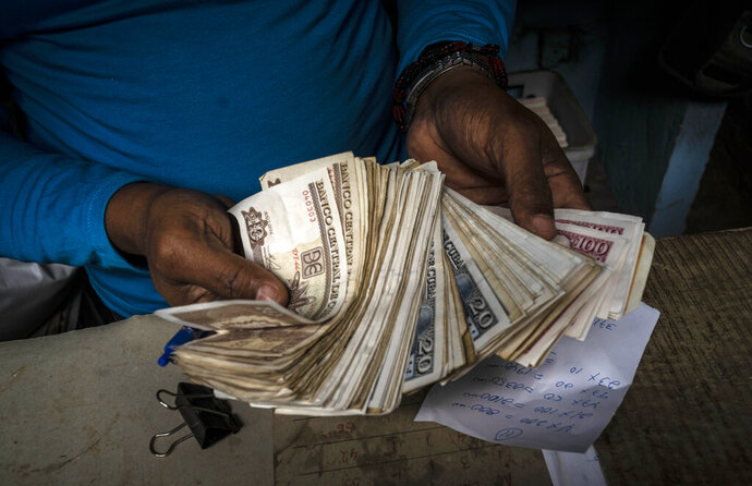 FILE - In this Dec. 11, 2020 file photo, a worker shows a wad of Cuban pesos in Havana, Cuba, Friday, Dec. 11, 2020. In 2021, the government is implementing a deep financial reform that reduces subsidies, eliminates a dual currency that was key to the old system, and raises salaries, in hopes of boosting productivity to help alleviate an economic crisis and reconfigure a socialist system that will still grant universal benefits such as free health care and education. (AP Photo/Ramon Espinosa, File)