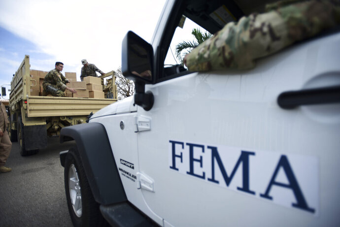 FILE - In this Oct. 5, 2017 file photo, Department of Homeland Security personnel deliver supplies to Santa Ana community residents in the aftermath of Hurricane Maria in Guayama, Puerto Rico. Federal authorities said Tuesday, Sept. 10, 2019, that they have arrested two former officials of the Federal Emergency Management Authority and the former president of a major disaster relief contractor, accusing them of bribery and fraud in the efforts to restore electricity to Puerto Rico in the wake of Hurricane Maria. (AP Photo/Carlos Giusti, File)
