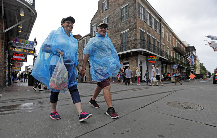 Alan and Dot Richardson, from England, wear ponchos as they walk along Bourbon Street in the French Quarter Friday, July 12, 2019, in New Orleans, ahead of Tropical Storm Barry. The National Weather Service in New Orleans says water is already starting to cover some low lying roads as Tropical Storm Barry approaches the state from the Gulf of Mexico. (AP Photo/David J. Phillip)