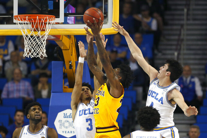 Arizona State forward Romello White, center, shoots under pressure from UCLA guards Jules Bernard (3) and Jaime Jaquez Jr. (4) during the first half of an NCAA college basketball game Thursday, Feb. 27, 2020, in Los Angeles. (AP Photo/Ringo H.W. Chiu)