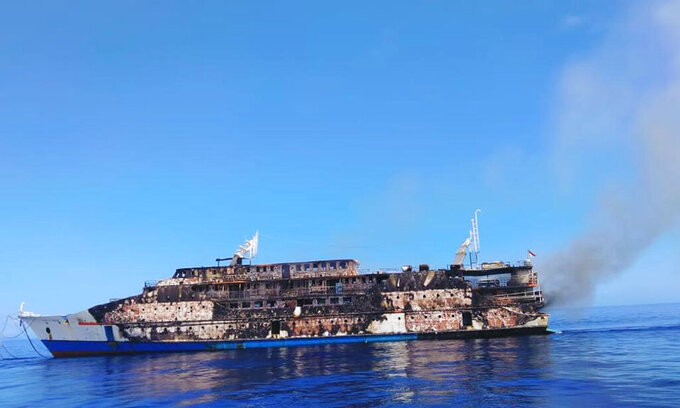 This Saturday, May 29, 2021, photo released by the National Search and Rescue Agency (BASARNAS), smoke billows from the wreckage of KM Karya Indah ferry after it caught fire off Limafatola Island, Indonesia. The ferry in eastern Indonesia caught fire early Saturday with nearly 200 people on board, forcing passengers and crew to jump into the sea but causing no casualties, officials said. (BASARNAS via AP)