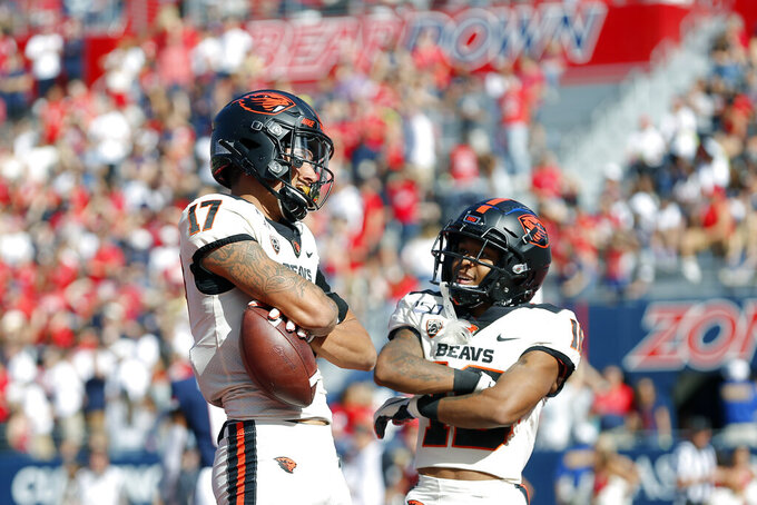 Oregon State wide receiver Isaiah Hodgins (17) celebrates with Champ Flemings (16) after scoring a touchdown in the first half during an NCAA college football game against Arizona, Saturday, Nov. 2, 2019, in Tucson, Ariz. (AP Photo/Rick Scuteri)