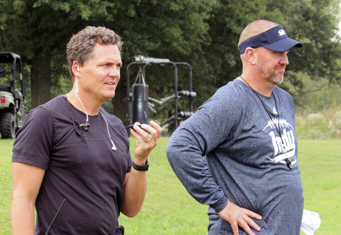 "In this 2017 file photo, director Greg Whiteley, left, and Independence Community College football coach Jason Brown watch a practice during a shoot for the Netflix series ""Last Chance U."" in Independence, Kan. Jason Brown has resigned after an inflammatory series of text messages in which he allegedly told a German player: ""I'm your new Hitler."" Brown said in a statement posted on social media that a story on the texts in the Montgomery County Chronicle made it ""nearly impossible to stay"" at Independence Community College. (Dion Lefler/The Wichita Eagle via AP, File)"