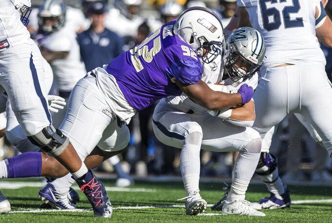 James Madison defensive lineman Mike Greene (92) wraps up Monmouth running back Pete Guerriero (25) during the first half of a second-round game in the NCAA Football Championship Subdivision playoffs Saturday, Dec. 7, 2019, in Harrisonburg, Va. (Daniel Lin/Daily News-Record via AP)