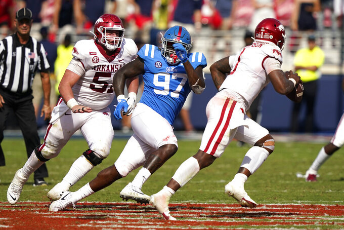 Mississippi defensive lineman Jamond Gordon (97) forces Arkansas quarterback KJ Jefferson (1) to scramble during the second half of an NCAA college football game, Saturday, Oct. 9, 2021, in Oxford, Miss. Mississippi won 52-51.(AP Photo/Rogelio V. Solis)