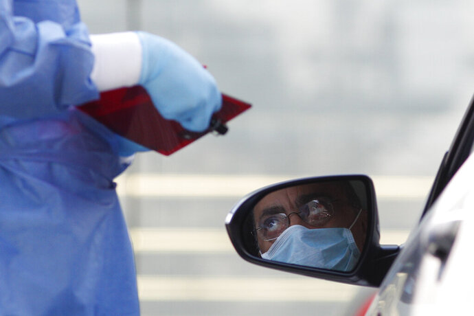 A doctor gathers information from a driver arriving to get tested for COVID-19 at private laboratory Biomedica de Referencia, in the Lomas Virreyes neighborhood of Mexico City, Thursday, March 26, 2020. The new coronavirus causes mild or moderate symptoms for most people, but for some, especially older adults and people with existing health problems, it can cause more severe illness or death. (AP Photo/Rebecca Blackwell)