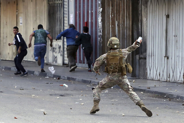 A Lebanese army soldier throws a tear gas canister towards anti-government protesters in the northern city of Tripoli, Lebanon, Tuesday, April 28, 2020. Hundreds took part in the funeral of a young man killed in riots overnight in Tripoli that were triggered by the crash of Lebanon's national currency that sent food prices soaring. (AP Photo/Bilal Hussein)