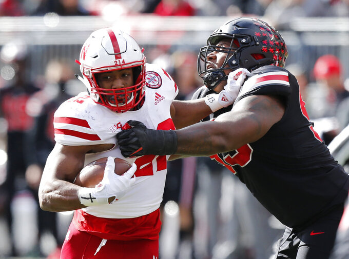 Nebraska running back Devine Ozigbo, left, tries to escape the grasp of Ohio State defensive lineman Davon Hamilton during the first half of an NCAA college football game Saturday, Nov. 3, 2018, in Columbus, Ohio. (AP Photo/Jay LaPrete)