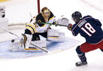 Boston Bruins goaltender Tuukka Rask (40) makes a save on Columbus Blue Jackets center Pierre-Luc Dubois (18) during the first period of an exhibition NHL hockey game Thursday, July 30, 2020 in Toronto. (Frank Gunn/The Canadian Press via AP)