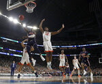 Auburn's Jared Harper (1) goes up for a basket against Virginia's De'Andre Hunter (12) during the first half in the semifinals of the Final Four NCAA college basketball tournament, Saturday, April 6, 2019, in Minneapolis. (AP Photo/David J. Phillip)