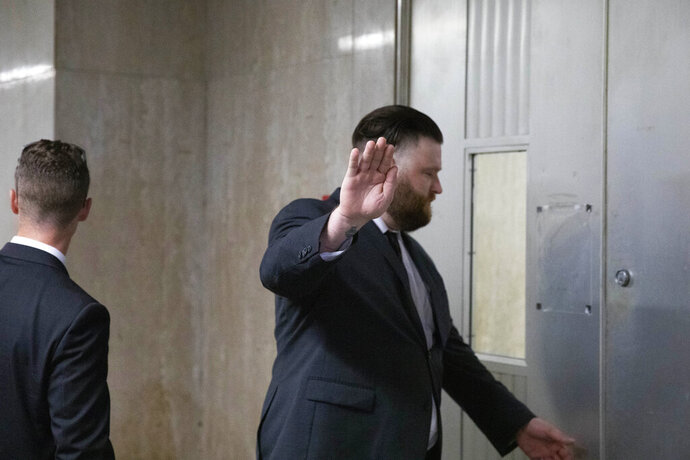 FILE - In this July 31, 2019, file photo, John Kinsman, right, puts his hand up to obscure his face from members of the media as he and Maxwell Hare, left, arrive at court for their trial in New York. On Monday, Aug. 19, 2019, the two members of the far-right Proud Boys group were found guilty of charges, including attempted gang assault, for their roles in a violent clash with left-wing protesters following a speech at the Metropolitan Republican Club in New York. (AP Photo/Mark Lennihan, File)