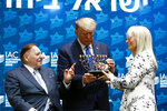 President Donald Trump receives a menorah from Las Vegas Sands Corporation Chief Executive and Republican mega donor Sheldon Adelson, left, and his wife Miriam Adelson at the Israeli American Council National Summit in Hollywood, Fla., Saturday, Dec. 7, 2019. (AP Photo/Patrick Semansky)