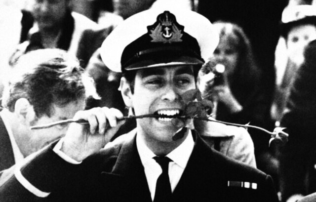 FILE - In this Sept. 16, 1982, file photo, Britain's Prince Andrew bites the stem of a red rose, after stepping ashore at Portsmouth, England, from the aircraft carrier HMS Invincible. A red rose was presented to each member of the Invincible's crew, as they left the vessel after her record 166 days at sea, which included action in the Falklands conflict. (AP Photo/David Caulkin, File)