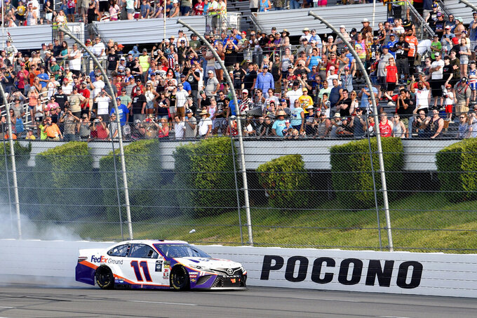 Denny Hamlin celebrates with a burnout after winning a NASCAR Cup Series auto race, Sunday, July 28, 2019, in Long Pond, Pa. (AP Photo/Derik Hamilton)