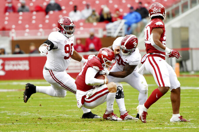 Alabama defenders Stephon Wynn Jr. (90) and Shane Lee (35) put the pressure on Arkansas quarterback Feleipe Franks as he is tackles for a loss during the second half of an NCAA college football game Saturday, Dec. 12, 2020, in Fayetteville, Ark. (AP Photo/Michael Woods)