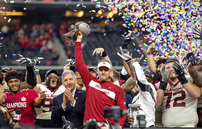 FILE - In this Dec. 1, 2018, file photo, Oklahoma head coach Lincoln Riley hoists the Big 12 Conference championship trophy after beating Texas 39-27 in the Big 12 Conference championship NCAA college football game, in Arlington, Texas. Riley was selected coach of the year when the AP All-Big 12 team was announced Friday, Dec. 7, 2018.  (AP Photo/Jeffrey McWhorter, File)