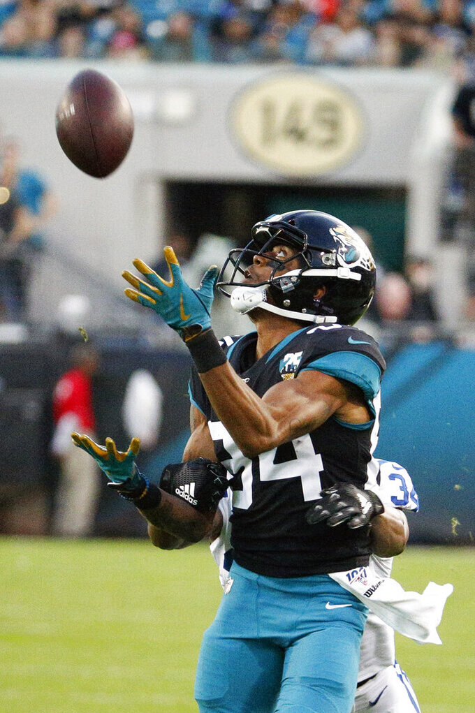 Jacksonville Jaguars wide receiver Keelan Cole, front, makes a reception in front of Indianapolis Colts cornerback Rock Ya-Sin during the first half of an NFL football game, Sunday, Dec. 29, 2019, in Jacksonville, Fla. (AP Photo/Stephen B. Morton)