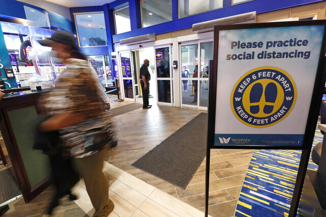 A patron rushes into the WaterView Casino and Hotel in Vicksburg, Miss., Thursday, May 21, 2020, for a morning of gaming, following a two-month shutdown due to coronavirus. Casinos statewide are allowed to reopen Thursday, amid enhanced restrictions to keep customers and employees safe. (AP Photo/Rogelio V. Solis)
