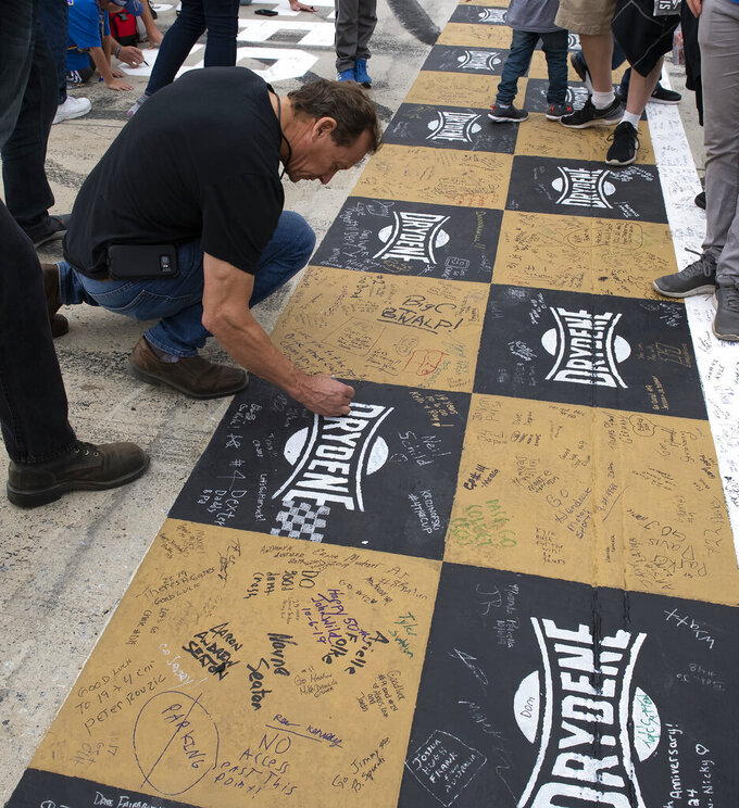 Kevin Schild, of Long Valley, N.J., writes a message on the start/finish line before the Drydene 400 - Monster Energy NASCAR Cup Series playoff auto race, Sunday, Oct. 6, 2019, at Dover International Speedway in Dover, Del. (AP Photo/Jason Minto)