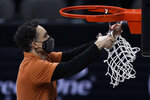 Texas head coach Shaka Smart cuts down the net after winning the Big 12 Tournament Championship NCAA college basketball game against Oklahoma State in Kansas City, Mo, Saturday, March 13, 2021.  (AP Photo/Charlie Riedel)