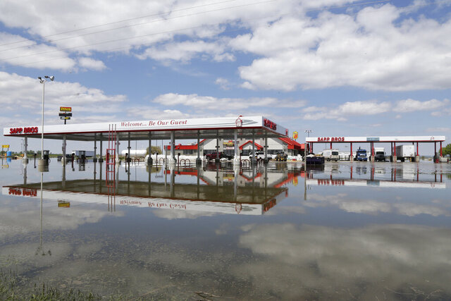 FILE - In this May 10, 2019 file photo, a Sapp Bros. gas station in Percival, Iowa, stands in floodwaters from the Missouri River. Republican senators from four states that have seen severe flooding from the Missouri River are backing legislation that would require the U.S. Army Corps of Engineers to change its management of the river to reduce flooding risk.The measure, which was introduced Thursday, March, 5, 2020, follows criticism from residents of flooded areas that the Corps should give flood protection a higher priority than environmental, recreational and other needs. (AP Photo/Nati Harnik, File)