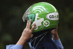 A woman holds a Gojek helmet after arriving at a station in Jakarta, Indonesia, Monday, May 17, 2021. Indonesian ride hailing company Gojek and e-commerce firm Tokopedia said Monday that they are merging, in the largest ever deal in the country's history. (AP Photo/Achmad Ibrahim)