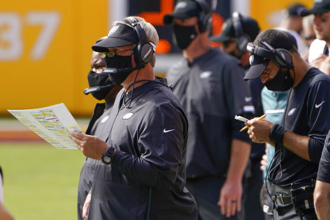 Philadelphia Eagles head coach Doug Pederson and members of his coach staff work on the sidelines wearing mask during the second half of an NFL football game against the Washington Football Team, Sunday, Sept. 13, 2020, in Landover, Md. (AP Photo/Susan Walsh)