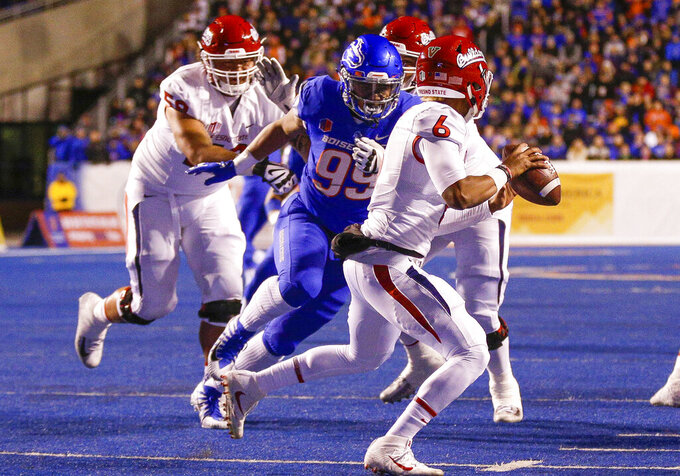 FILE - In this Nov. 9, 2018, file photo, Boise State's Curtis Weaver (99) closes in on Fresno State quarterback Marcus McMaryion (6) in the first half of an NCAA college football game in Boise, Idaho.  The Broncos have the preseason MWC defensive player of the year in Curtis Weaver, who collected 9 ½ sacks last season. (AP Photo/Steve Conner, File)