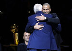 Former San Antonio Spurs guard Tony Parker, right, hugs former coach Gregg Popovich during Parker's retirement ceremony after the team's NBA basketball game against the Memphis Grizzlies in San Antonio, Monday, Nov. 11, 2019. (AP Photo/Eric Gay)