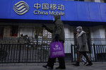 Residents pass by a branch of the China Mobile Ltd. in Beijing on Jan. 8, 2021. Profit at state-owned companies that dominate China's banking, oil and most other industries rose by as much as 25% last year as the country recovered from the coronavirus pandemic, according to the. State-Owned Assets Supervision and Administration Commission which oversees 97 companies directly under the Cabinet including PetroChina Ltd., Asia's biggest oil producer; China Mobile Ltd., the world's biggest phone carrier by number of subscribers, and Industrial and Commercial Bank of China Ltd., the world's biggest bank by assets. (AP Photo/Ng Han Guan)