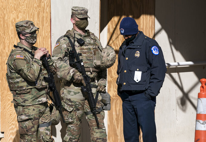 A U.S. Capitol Police officer, right, stands with two National Guard members near the scene where a fellow officer was killed after a man rammed a car into two officers at a barricade outside the U.S. Capitol and then emerged wielding a knife, on Capitol Hill in Washington, Friday, April 2, 2021. (AP Photo/J. Scott Applewhite)
