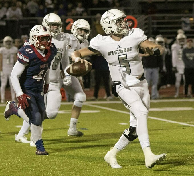 In this Nov. 6, 2018, photo, Blue Valley North High School quarterback Graham Mertz (5) throws against Olathe during a high school football game in Olathe, Kansas. Wisconsin freshman Graham Mertz is the most hyped recruit in years, having enrolled in January after setting a Kansas high school record for touchdown passes last season and being named MVP of the U.S. Army All-American Bowl. Mertz is competing for the Wisconsin starters job. (Susan Pfannmuller/The Kansas City Star via AP)