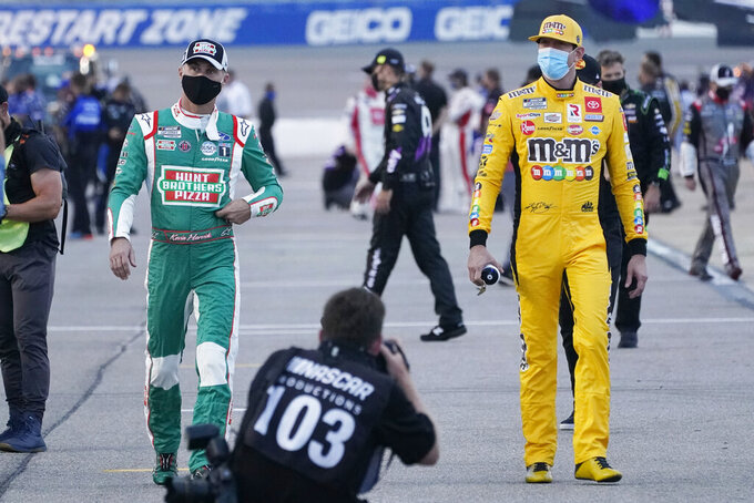 Kevin Harvick, left, and Kyle Busch, right, walk to their cars prior to the start of a NASCAR Cup Series auto race Saturday, Sept. 12, 2020, in Richmond, Va. (AP Photo/Steve Helber)