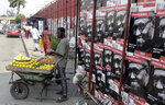 FILE - In this Thursday, Feb. 7, 2019 file photo, a vendor sell oranges in front of campaign posters of Nigeria's incumbent President Muhammadu Buhari of the All Progressives Congress Party, on a street in Lagos, Nigeria. Nigeria's government is acknowledging a resurgence of Islamic extremist violence. The near-daily attacks have many traumatized Nigerians questioning whether they can vote for President Muhammadu Buhari on Saturday Feb. 16, 2019, as he seeks a second term. (AP Photo/Sunday Alamba, File)