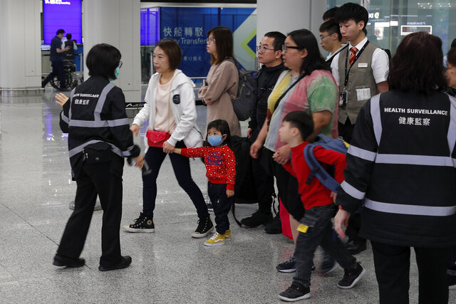 Health surveillance officer use device to check temperature of passengers before the immigration counters at International airport in Hong Kong, Saturday, Jan. 4, 2020. Hong Kong authorities activated a newly created