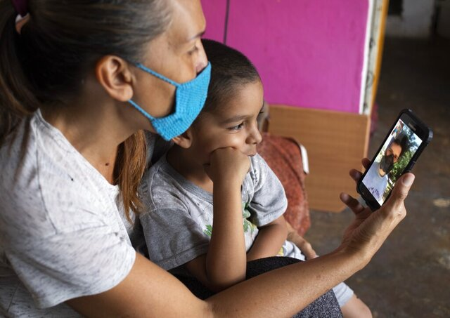 In this April 27, 2020 photo, Daniel sits in grandmother's lap in their apartment in Caracas, Venezuela, as they chat via a messenger service with his father Misael Cocho. After fleeing Venezuela along with millions of others amid the country's grueling humanitarian crisis, Cocho made his way by bus to Peru — where he got odd jobs and sent money home monthly to support his mother and his 5-year-old son. But just after Cocho landed his steadiest work so far in Lima, the new coronavirus cases skyrocketed. He lost his job. (AP Photo/Ariana Cubillos)