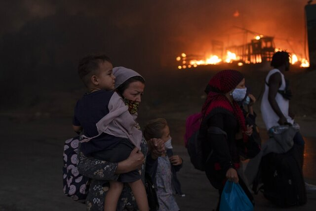 Migrants flee from the Moria refugee camp during a second fire, on the northeastern Aegean island of Lesbos, Greece, on Wednesday, Sept. 9, 2020. Fire struck again Wednesday night in Greece's notoriously overcrowded refugee camp on the island of Lesbos, a day after a blaze swept through it and left thousands in need of emergency shelter. The fires caused no injuries, but they renewed criticism of Europe's migration policy. (AP Photo/Petros Giannakouris)