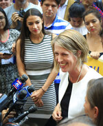 Alexandria Ocasio-Cortez, center, the surprise winner in the congressional race who unseated 20-year incumbent Joe Crowley in New York's Congressional District 14, listens to Zephyr Teachout, right, during a press conference, after endorsing her candidacy for Attorney General, Thursday, July 12, 2018, in New York. (AP Photo/Bebeto Matthews)